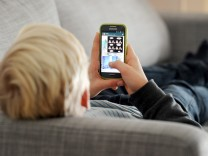 Ein Jugendlicher mit Smartphone - der Messenger-Dienst Whatsapp kündigte 2018 an, das Mindestalter für Nutzer auf 16 Jahre zu erhöhen.
