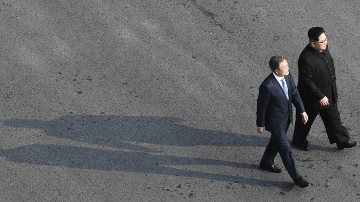 South Korean President Moon Jae-in and North Korean leader Kim Jong Un walk together at the truce village of Panmunjom