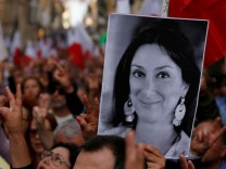 A demonstrator carries a photo of assassinated anti-corruption journalist Daphne Caruana Galizia as others sing the national anthem at the end of a protest against government corruption revealed by the Daphne Project, in Valletta