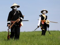 People dressed as characters from the computer game 'World of Warcraft' walk across a field near the town of Kamyk nad Vltavou