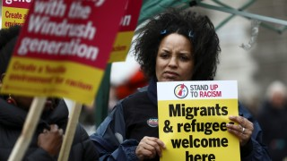 People hold placards during a demonstration to protest againt the treament of members of the Windrush generation, opposite the Houses of Parliament in London