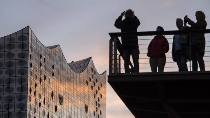 Touristen fotografieren während des Sonnenuntergangs die Elbphilharmonie in Hamburg.