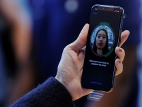 FILE PHOTO: A woman sets up facial recognition on her Apple iPhone X at an Apple store in New York
