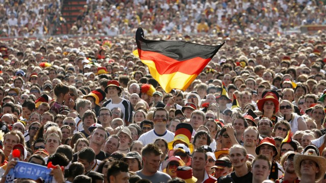 A soccer fan waves a German flag during a public screening of the World Cup soccer match between Germany and Argentina in Hamburg