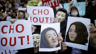 People hold portraits depicting Cho Hyun-ah and Cho Hyun-min, daughters of Korean Air Lines' chairman Cho Yang-ho as they take part in a protest against the abuse of power by them, in central Seoul