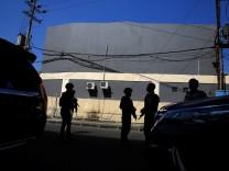 Anti-terror policemen stand guard following a bomb blast at a police office in Surabaya
