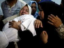 Relative mourns as she carries the body of 8-month-old Palestinian infant Laila al-Ghandour during her funeral in Gaza City