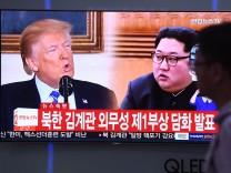 Donald Trump und Kim Jong-un auf einem Fensehbild in einem Bahnhof in Seoul - 2018 suchen die USA und Nordkorea einen Annäherung der beiden Staaten.