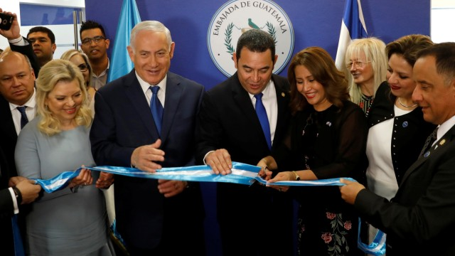 Hilda Patricia Marroquin, the wife of Guatemalan President Jimmy Morales, cuts the ribbon during the dedication ceremony of the embassy of Guatemala in Jerusalem, as she stands with Guatemalan President Jimmy Morales, Israeli Prime Minister Benjamin Netan