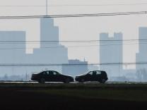 Zwei Autos auf einer Landstraße in Hessen - im Hintergrund sind im Dunst die Hochhäuser von Frankfurt am Main zu sehen.
