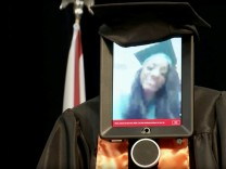 A robot with an iPad 'receiving' Hight School diploma as student Cynthia Pettway, who was unable to leave a hospital for the ceremony, is seen in Mobile, Alabama