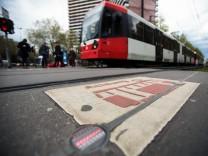 Ein Mensch läuft über eine Bodenampel, auch Bompel genannt, in Köln. Im Hintergrund wartet eine Straßenbahn.