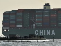 FILE PHOTO: Onlookers watch as the largest container ship in world, CSCL Globe, docks during its maiden voyage, at the port of Felixstowe in south east England