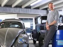 Filmautos in Berlin: Sven Liedtke von der Verleihfirma Moviecars neben einem VW Käfer und einem rostigen Pick-up von Chevrolet.