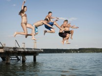 Five teenagers jumping from a jetty into lake mit_2003_00996