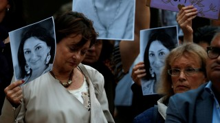 People hold up posters and pictures of assassinated anti-corruption journalist Daphne Caruana Galizia during a vigil and demonstration marking seven months since her murder in a car bomb, at her makeshift memorial outside the Courts of Justice in Valletta