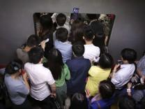 Pendler drängen in eine U-Bahn in Chinas Hauptstadt Peking.