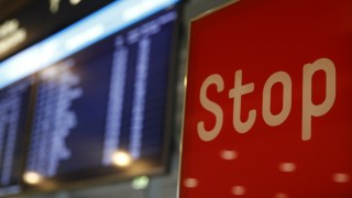 A sign reading Stop stands in front of an electronic information board following a security alert at Cologne airport