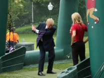 President Trump swings golf club as young participants look on during White House Sports and Fitness Day in Washington