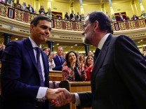 Spain's new Prime Minister and Socialist party (PSOE) leader Pedro Sanchez shakes hands with ousted Prime Minister Mariano Rajoy after a motion of no confidence vote at parliament in Madrid