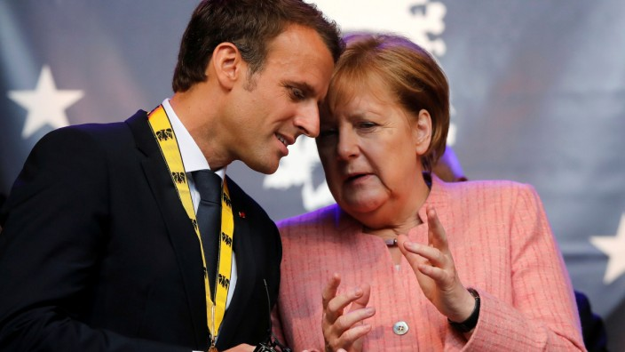 FILE PHOTO: French President Macron and German Chancellor Merkel wave after Macron was awarded Charlemagne Prize in Aachen