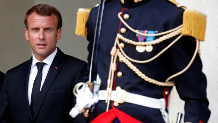 French President Emmanuel Macron stands next to a Republican Guard outside the Elysee Palace in Paris