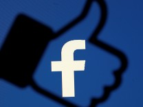 FILE PHOTO: A 3D-printed Facebook like button is seen in front of the Facebook logo, in this illustration