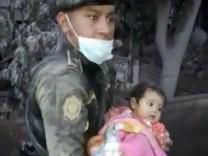Ein Soldat rettet nach dem Vulkanausbruch des Feuervulkans in Guatemala ein kleines Mädchen aus dem Krisengebiet.