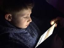 Kind Junge Schulkind schaut gebannt auf ein Tablet und liest schaut Filme an Smartphone Handy Comput