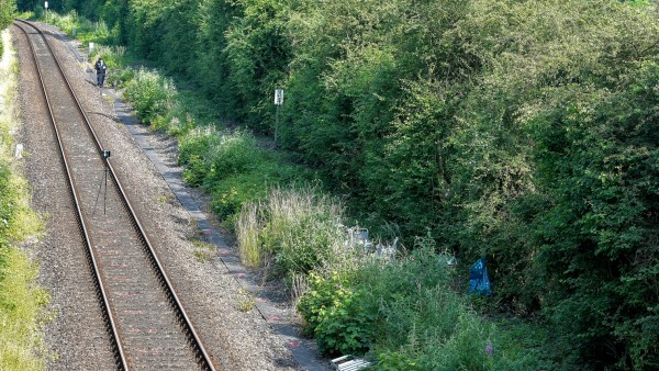 German police walk along a railway track towards the scene where they found a body near Wiesbaden-Erbenheim