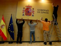 Workers set up a banner before a taking over ceremony at the Ministry of Economy in Madrid