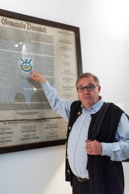 Bürgerhaus Dornach (Aschheim): 3. Bürgermeister Georg Hornburger vor der Urkunde mit den Dornacher Unternehmen Stand 1975, rund um das Dornacher Wappen (Symbolik: Dornen, Ähren, Zahnrad)