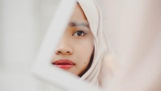 Frau mit Kopftuch vor Spiegel