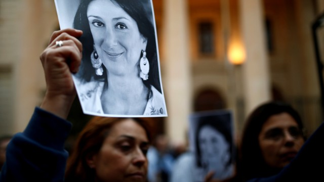 FILE PHOTO: People hold up pictures of assassinated anti-corruption journalist Daphne Caruana Galizia