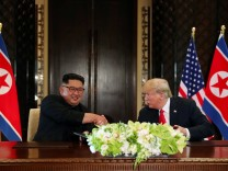 U.S. President Donald Trump and North Korea's leader Kim Jong Un shake hands after signing documents, at their summit in Singapore