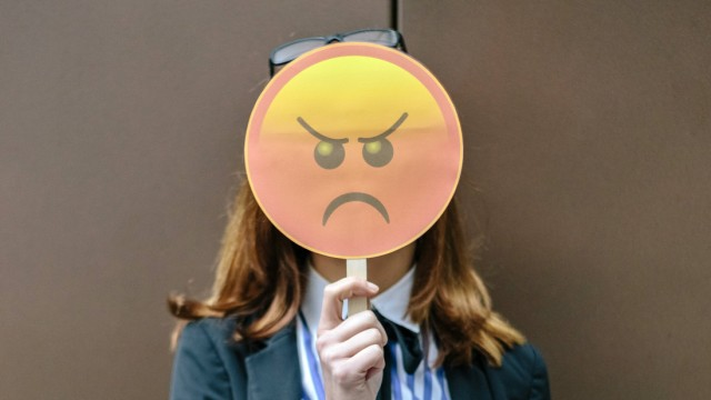 Woman hiding face behind emoji mask model released Symbolfoto property released PUBLICATIONxINxGERxS