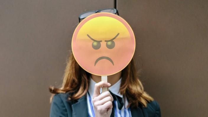 Woman hiding face behind emoji mask model released Symbolfoto property released PUBLICATIONxINxGERxS