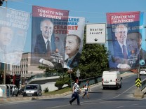 People walk under elelction posters for Turkey's President Tayyip Erdogan and Muharrem Ince, Presidential candidate of Turkey's main opposition Republican People's Party (CHP)  in Istanbul