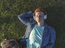 Redheaded young man with headphones lying on grass model released Symbolfoto PUBLICATIONxINxGERxSUIx