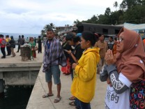 A woman prays for her son, a passenger on the KM Sinar Bangun ferry which sank yesterday in Lake Toba, in Simalungun, North Sumatra