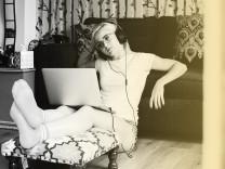 Eine junge Frau sitzt mit Kopfhörern vor ihrem Laptop.