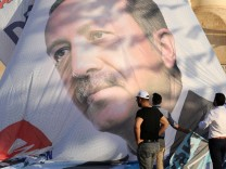 Workers adjust a large election poster of President Tayyip Erdogan in Mardin