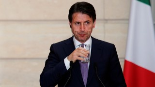 Italian Prime Minister Giuseppe Conte holds a glass of water during a joint news conferenece with French President Emmanuel Macron (not pictured) at the Elysee Palace in Paris