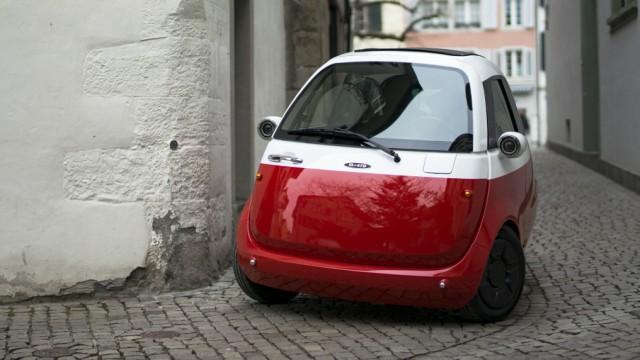 Das Elektroauto Microlino biegt auf einer Pflasterstraße um eine Häuserecke.