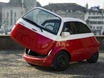 Elektroauto Microlino im Stil der BMW Isetta mit offener Kühlschranktür.