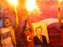 Supporters of Turkish President Tayyip Erdogan light torches in front of a Turkish flag, in front of Turkey's ruling AK Party (AKP) headquarters in Istanbul