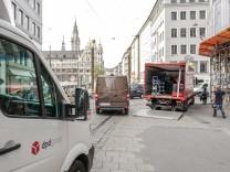 Auf der Theatinerstraße fährt ein Transporter an einem Laster vorbei.