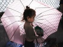 Kleines Mädchen wartet mit ihrer Mutter an der mexikanischen Grenze auf die Einreise in die USA.