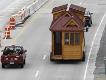 A Tumbleweed brand Cypress 24 model Tiny House is towed down the highway near Boulder
