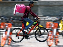A food delivery driver for Foodora cycles in downtown Milan